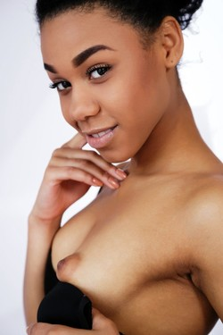 Young ebony model slowly undressing in..